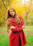 Forme a la mujer vestida en capa roja en parque del otoño Fotografía de archivo