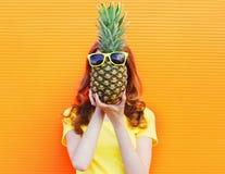 Forme la mujer y la piña del retrato con las gafas de sol sobre naranja colorida Foto de archivo