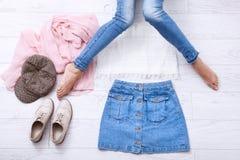 Forme la ropa con diversos accesorios y las piernas femeninas en vaqueros en el fondo de madera blanco Espacio de la visión super Fotografía de archivo libre de regalías