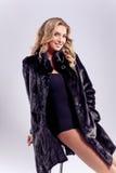 Forme a la señora atractiva del pelo rubio en un abrigo de pieles elegante y una ropa interior negra, sentándose en el taburete d fotos de archivo