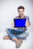 Forme la sentada del hombre mientras que le muestra la pantalla de ordenador Imágenes de archivo libres de regalías