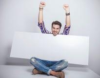 Forme la sentada del hombre mientras que sostiene una cartelera vacía Foto de archivo libre de regalías