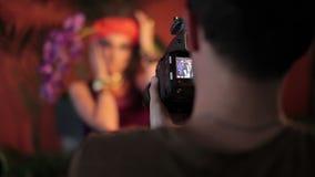 Forme la sesión fotográfica con el fotógrafo y el modelo femenino hermoso almacen de video