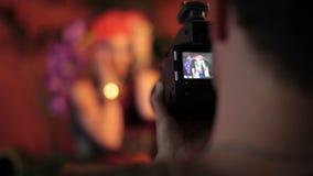 Forme la sesión fotográfica con el fotógrafo y el modelo femenino hermoso metrajes