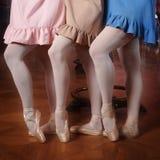 Forme a las bailarinas en los vestidos coloridos que hacen el pas Imagen de archivo libre de regalías