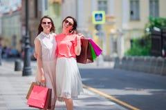 Forme a las chicas jóvenes con los panieres que caminan a lo largo de la calle de la ciudad Venta, consumerismo y concepto de la  Fotografía de archivo libre de regalías