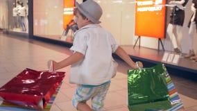 Forme las compras, niño de los clientes con los paquetes en funcionamientos de las manos a través del centro comercial después de almacen de metraje de vídeo