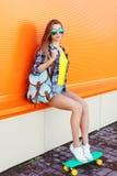 Forme las gafas de sol que llevan de la muchacha bastante fresca con el monopatín imágenes de archivo libres de regalías