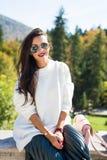 Forme las gafas de sol que llevan del retrato hermoso de la mujer, el suéter blanco y la falda verde fotos de archivo libres de regalías