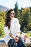 Forme las gafas de sol que llevan del retrato hermoso de la mujer, el suéter blanco y la falda verde fotos de archivo