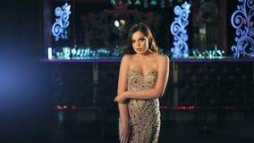 Forme a las mujeres jovenes que presentan en vestido hermoso en fondo de las luces de neón de la noche metrajes