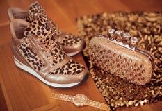 Forme las zapatillas de deporte del leopardo con el reloj y el monedero de oro del encanto en fondo de madera Imagenes de archivo