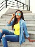 Forme a llevar africano sonriente hermoso de la mujer las gafas de sol y la ropa de los vaqueros Imágenes de archivo libres de regalías