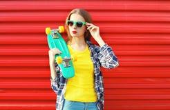 Forme a llevar bastante fresco de la muchacha las gafas de sol con el monopatín Imagen de archivo