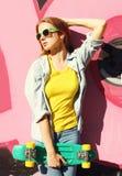 Forme a llevar bastante fresco de la muchacha las gafas de sol, la camisa de los vaqueros y el monopatín en ciudad sobre colorido Fotos de archivo libres de regalías