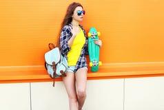 Forme a llevar bastante fresco de la muchacha las gafas de sol y la mochila con el monopatín sobre naranja Foto de archivo