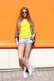 Forme a llevar bastante fresco de la muchacha las gafas de sol y los pantalones cortos en ciudad sobre colorido Imagenes de archivo