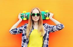 Forme a llevar bastante rubio de la muchacha las gafas de sol con el monopatín Fotos de archivo libres de regalías