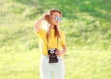 Forme a llevar bastante rubio de la mujer las gafas de sol con la cámara Foto de archivo