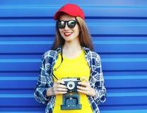 Forme a llevar bastante sonriente de la muchacha la ropa colorida con la cámara retra sobre azul Imagen de archivo libre de regalías