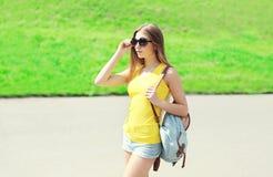 Forme a llevar bonito de la chica joven las gafas de sol y la mochila Fotos de archivo libres de regalías