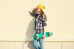 Forme a llevar bonito de la muchacha la ropa colorida con el monopatín Imágenes de archivo libres de regalías
