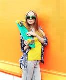Forme a llevar bonito de la muchacha las gafas de sol con el monopatín Fotos de archivo