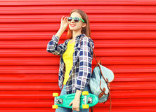 Forme a llevar bonito de la muchacha las gafas de sol, monopatín Imagen de archivo