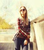 Forme a llevar bonito de la mujer las gafas de sol y la camisa a cuadros en ciudad Foto de archivo libre de regalías