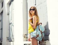 Forme a llevar de la mujer bastante joven las gafas de sol y la mochila Imagen de archivo libre de regalías