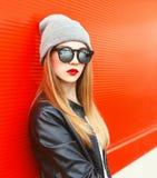 Forme a llevar de la mujer del retrato las gafas de sol, sombrero sobre rojo Fotos de archivo libres de regalías