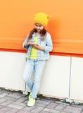 Forme a llevar del niño de la niña la ropa de los vaqueros usando smartphone sobre naranja Imagenes de archivo