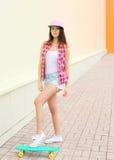 Forme a llevar fresco de la muchacha la ropa rosada colorida con el monopatín Imagenes de archivo