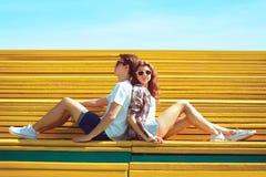 Forme a los adolescentes jovenes de los pares que descansan en el parque de la ciudad que se sienta en el banco Foto de archivo libre de regalías