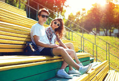 Forme a los adolescentes jovenes de los pares que descansan en la ciudad en banco en el verano Foto de archivo libre de regalías