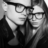 Forme a los gemelos en ropa negra y gafas de moda Imagen de archivo libre de regalías