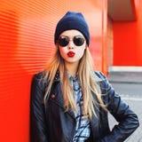 Forme los labios que soplan de la mujer con el estilo negro de la roca del lápiz labial que lleva rojo que se divierte en ciudad Imagen de archivo
