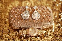Forme los pendientes y el reloj de oro, accessori para mujer del diamante Imagenes de archivo
