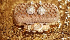 Forme los pendientes y el reloj de oro, accessori para mujer del diamante Foto de archivo libre de regalías
