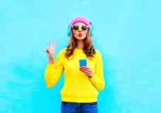 Forme a música de escuta da mulher despreocupada consideravelmente doce nos fones de ouvido com o smartphone que veste uma camise Imagens de Stock Royalty Free