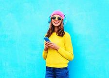 Forme a música que escucha de la mujer despreocupada bastante dulce en auriculares con smartphone las gafas de sol rosadas colori Imagenes de archivo