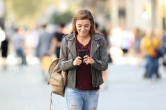 Forme mandar un SMS que camina de la muchacha en un teléfono en la calle Imagen de archivo