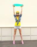 Forme a menina consideravelmente fresca com o skate que tem o divertimento sobre o branco Foto de Stock Royalty Free