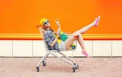 Forme a menina consideravelmente fresca no carro do trole que tem o divertimento sobre a laranja colorida Fotos de Stock