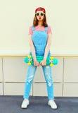 Forme a menina consideravelmente fresca que veste um fato-macaco da sarja de Nimes com um skate sobre o branco Foto de Stock Royalty Free
