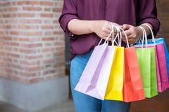 Forme a menina de compra, jovem mulher que leva sacos de compras coloridos ao andar ao longo do shopping foto de stock royalty free