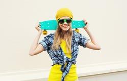 Forme a menina de sorriso consideravelmente fresca do retrato com o skate sobre o branco Foto de Stock Royalty Free