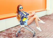 Forme a menina fresca no carro do trole da compra com skate imagens de stock royalty free