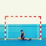 Forme a menina na roupa à moda no campo de futebol fotos de stock