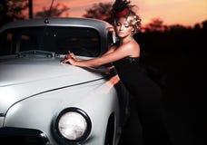 Forme a menina no estilo retro que levanta perto do carro velho foto de stock